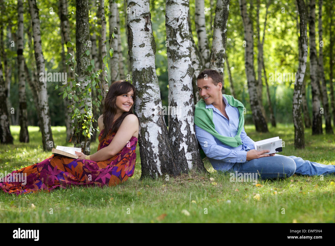 Young couple holding books in park by tree trunk, looking at each other Stock Photo