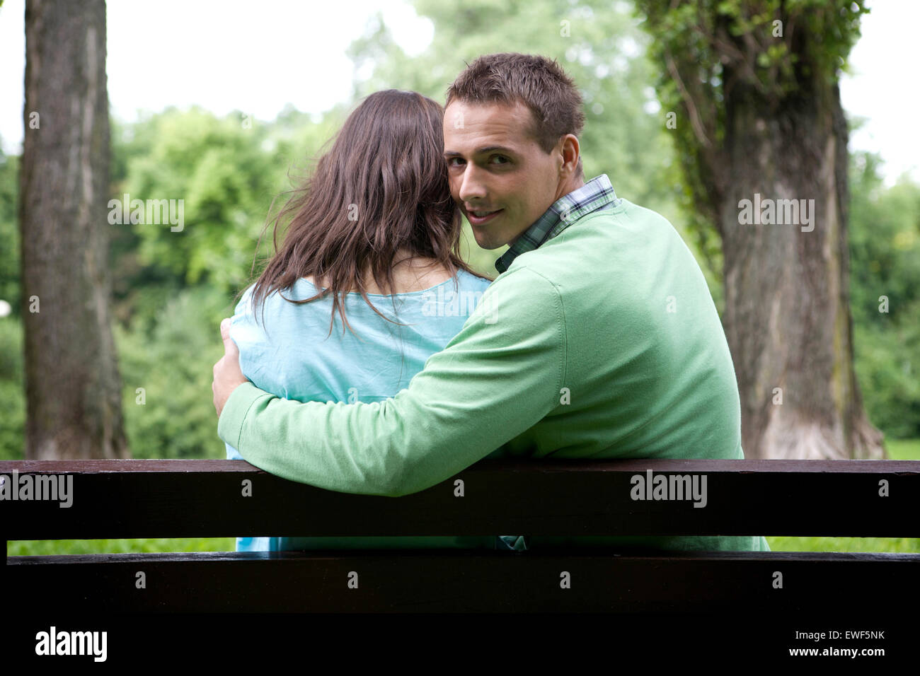 Portrait of young man with girlfriend sitting on bench - Stock Image