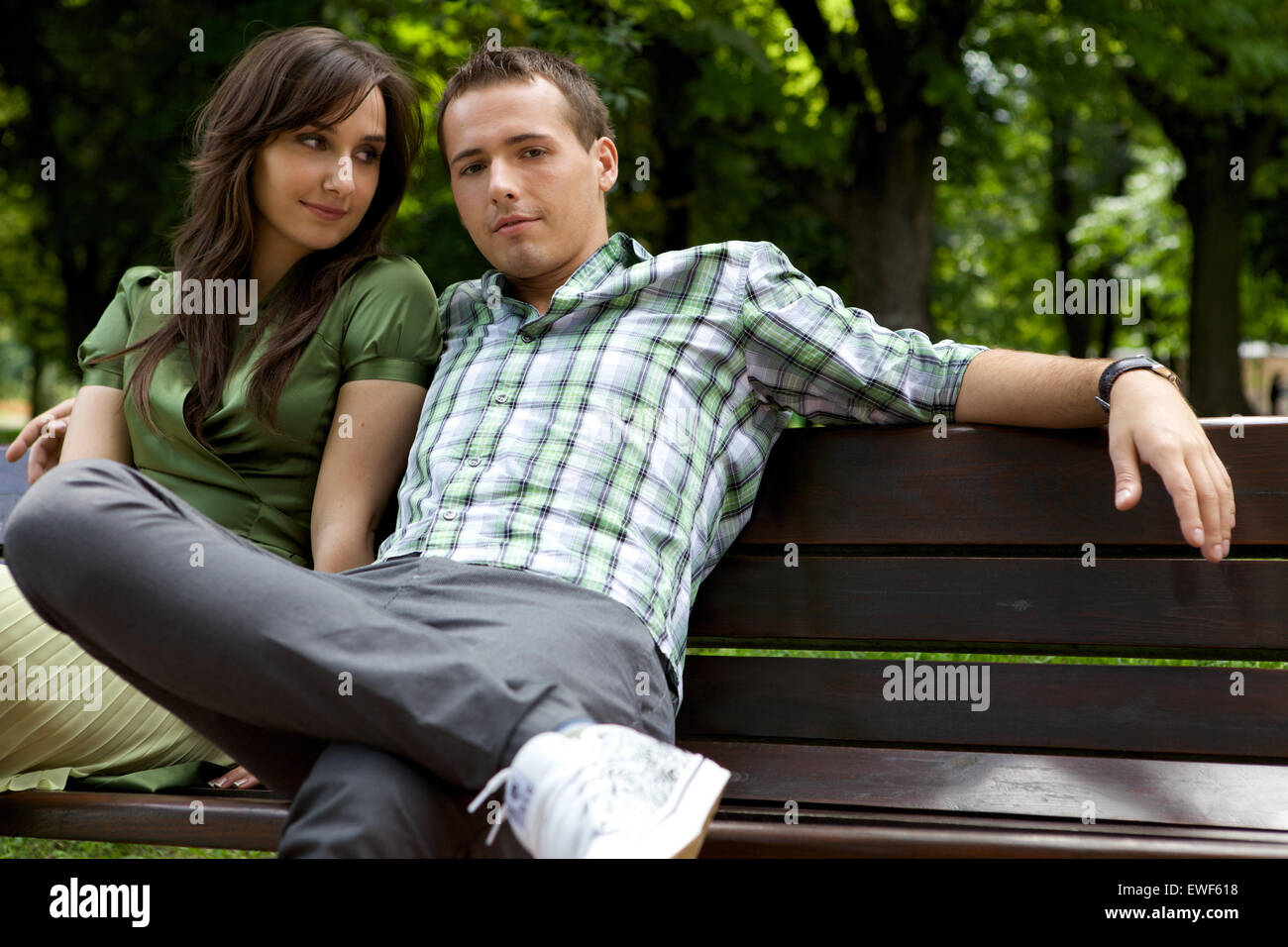 Young couple sitting on bench - Stock Image