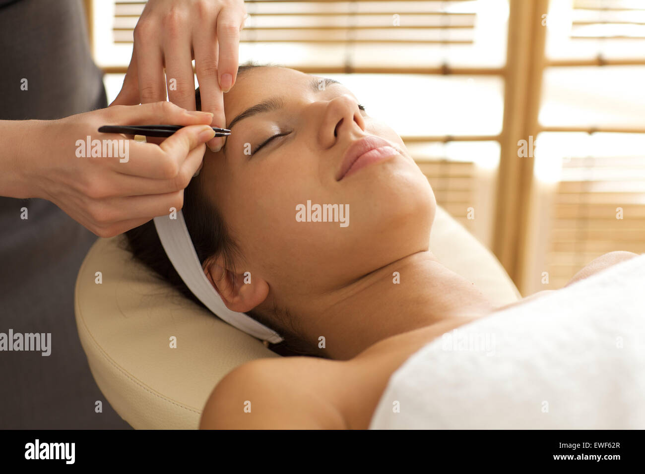 Young woman having eye-brows plucked - Stock Image