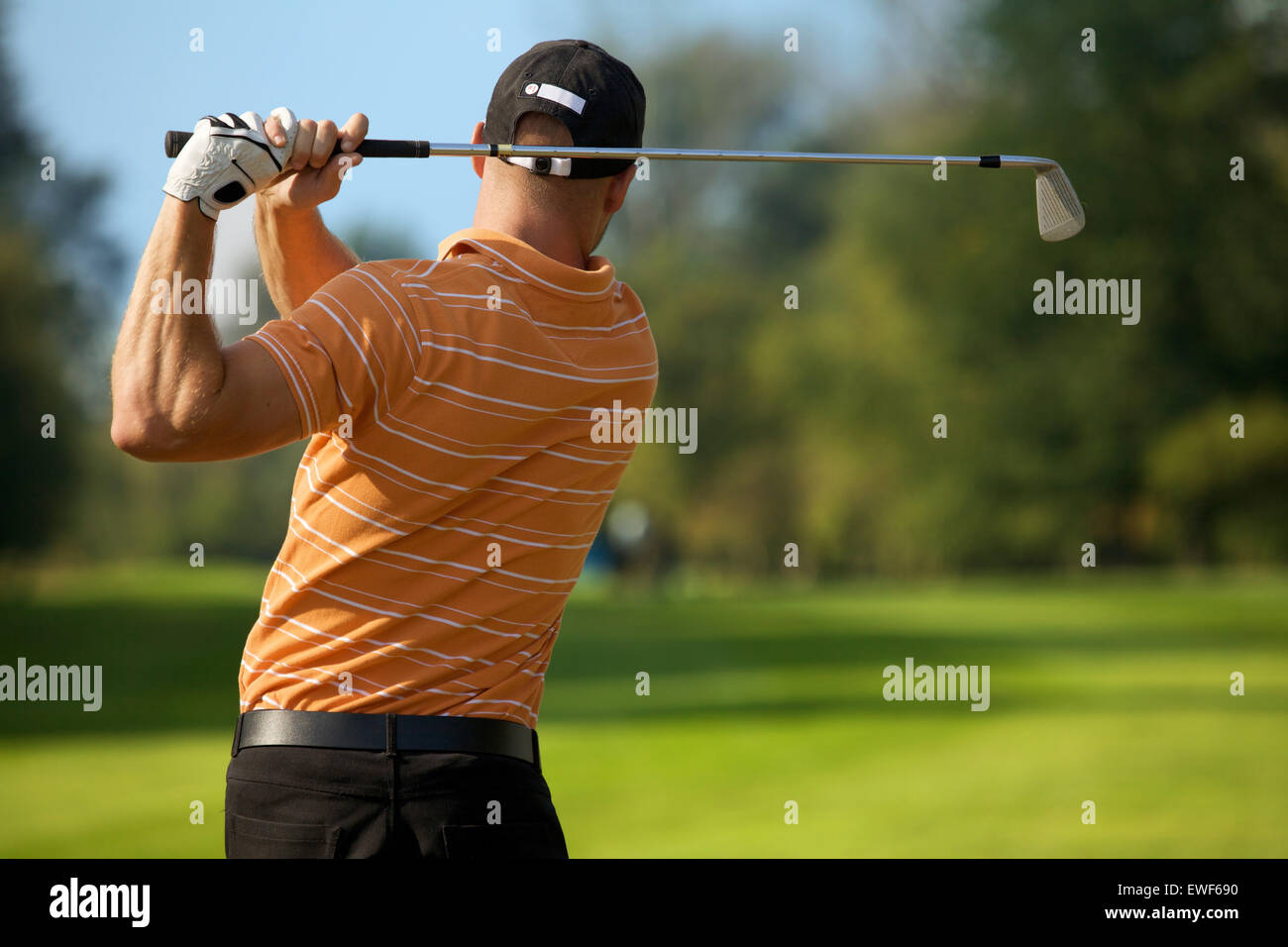 Young man swinging golf club, rear view - Stock Image