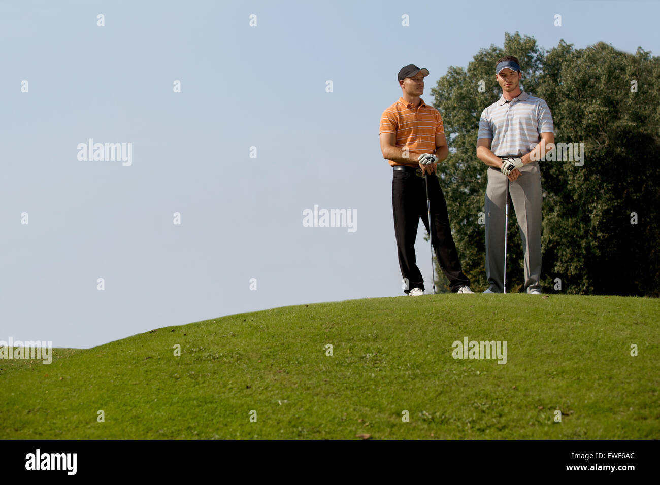 Portrait of young men standing with golf sticks on golf course - Stock Image