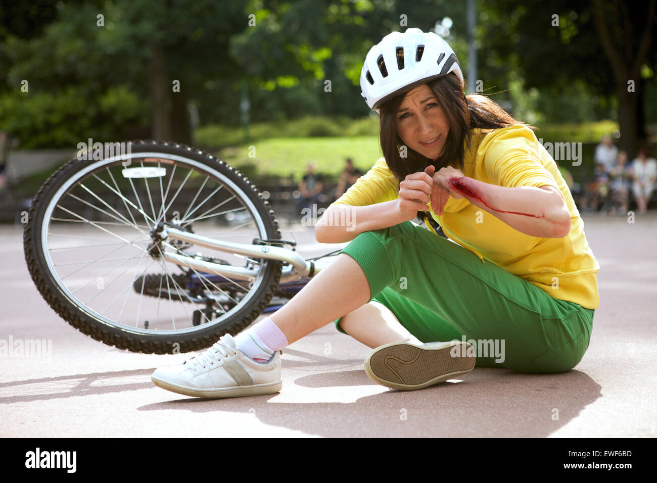 Young woman injured and clutching arm - Stock Image