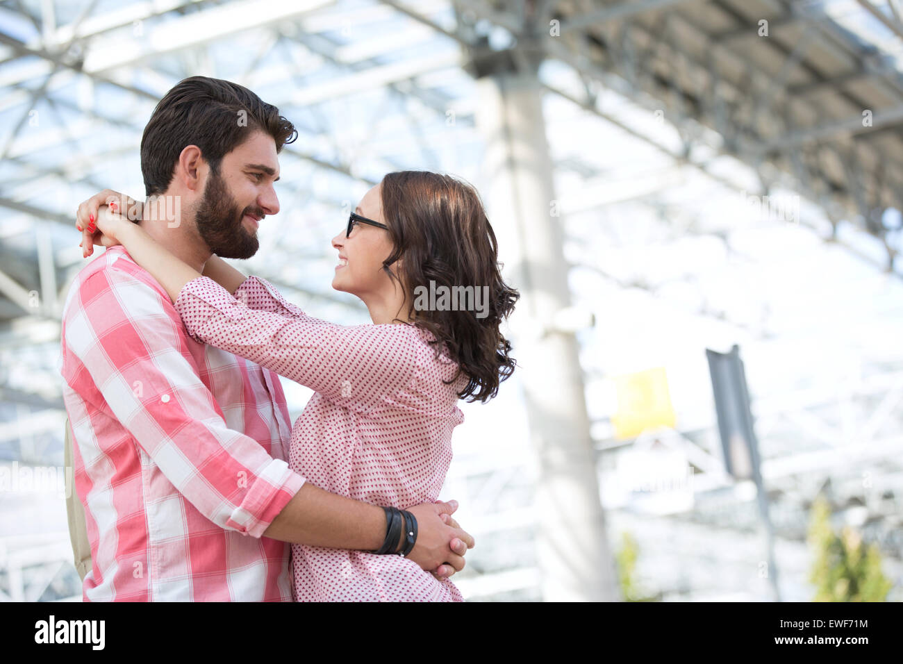 Loving couple looking at each other while embracing outside building - Stock Image