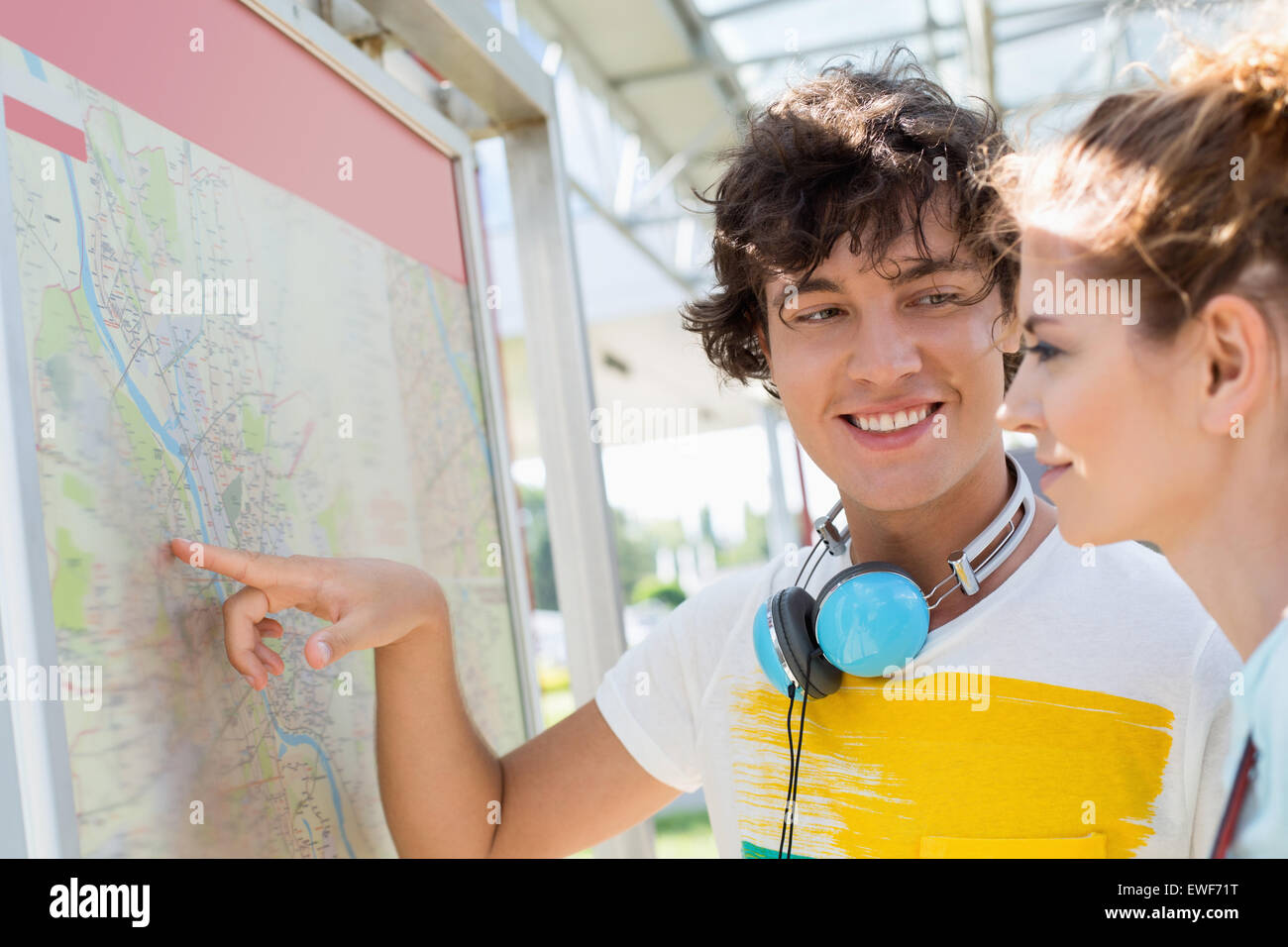 Happy man showing places on map to woman outdoors - Stock Image