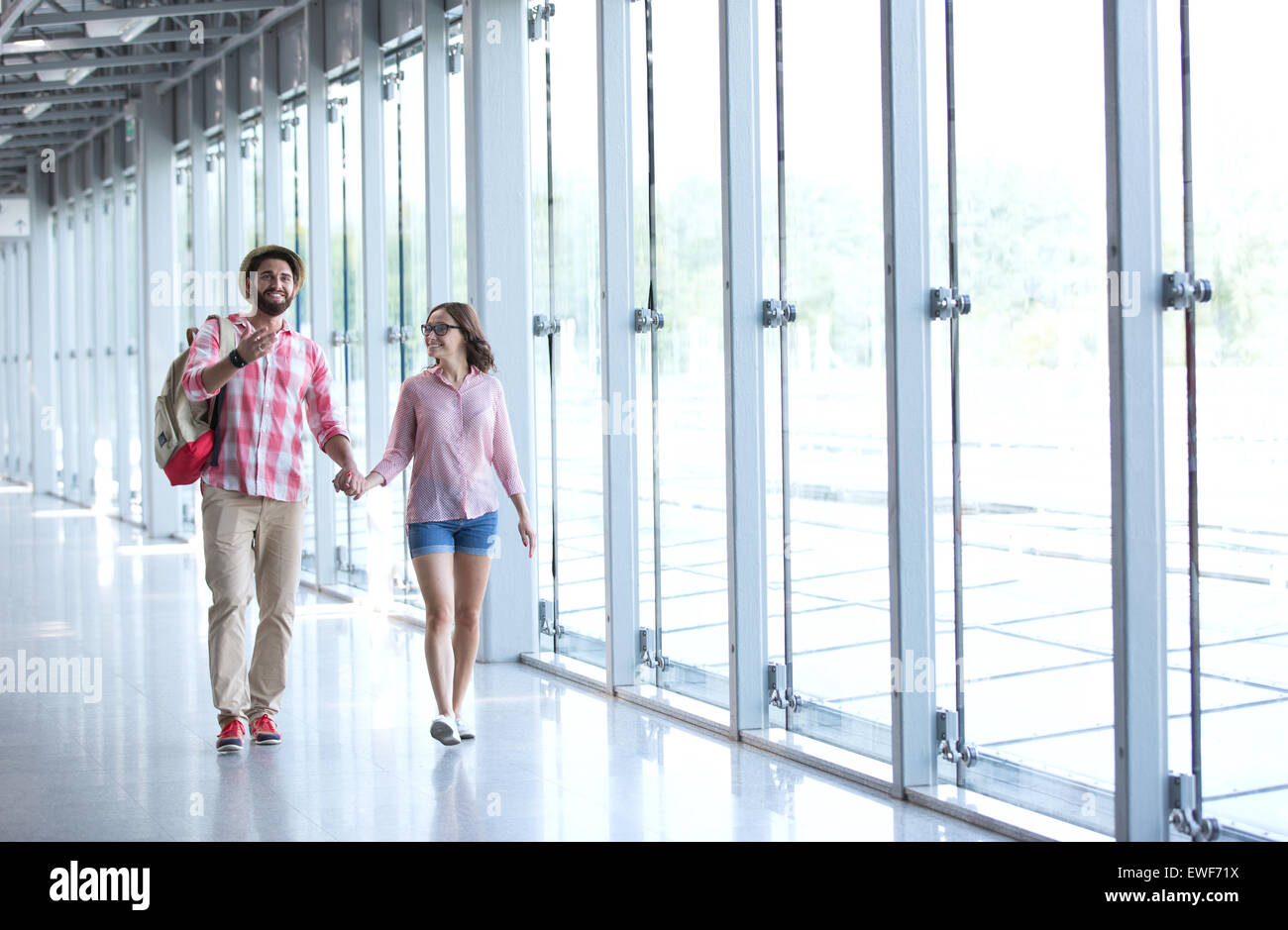 Full-length of couple holding hands while walking at covered passage - Stock Image