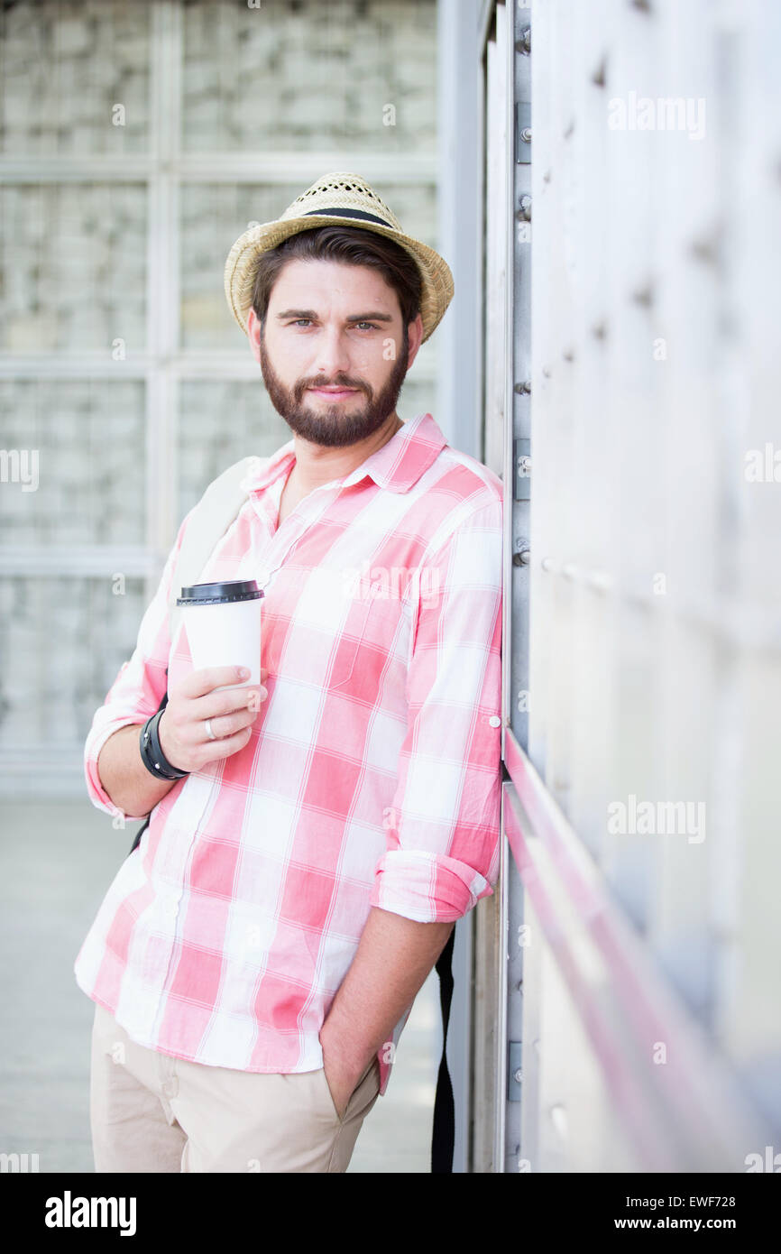 Portrait of confident man holding disposable cup while leaning on wall - Stock Image