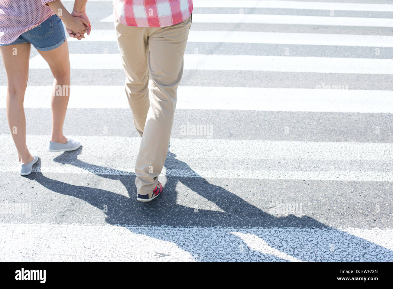 Low section of couple walking on crosswalk - Stock Image