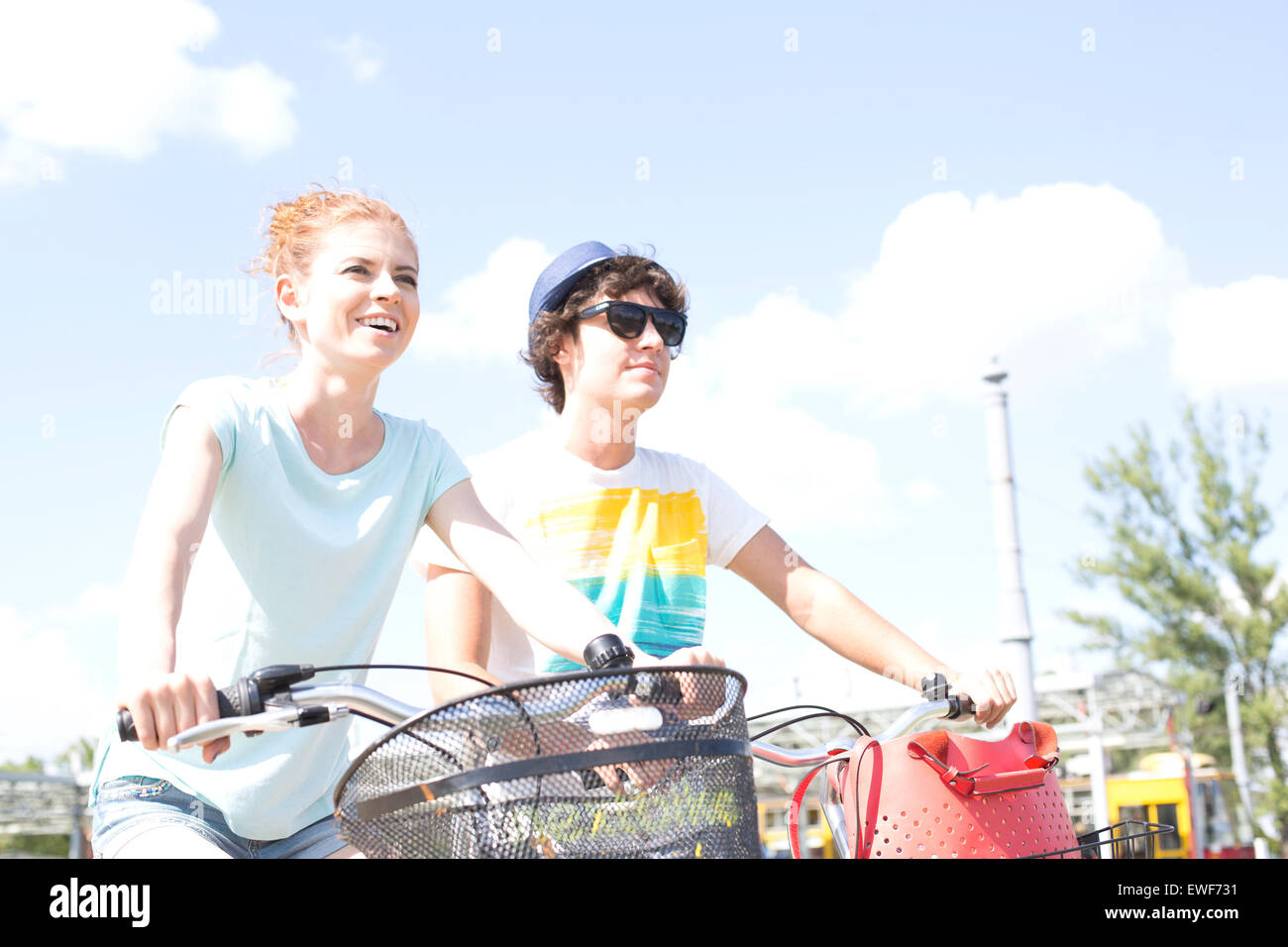 Smiling couple cycling against sky - Stock Image