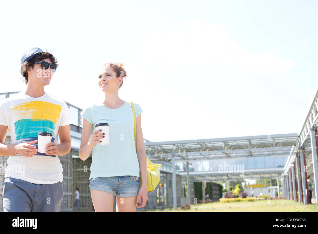 Couple holding disposable cups while walking at park - Stock Image