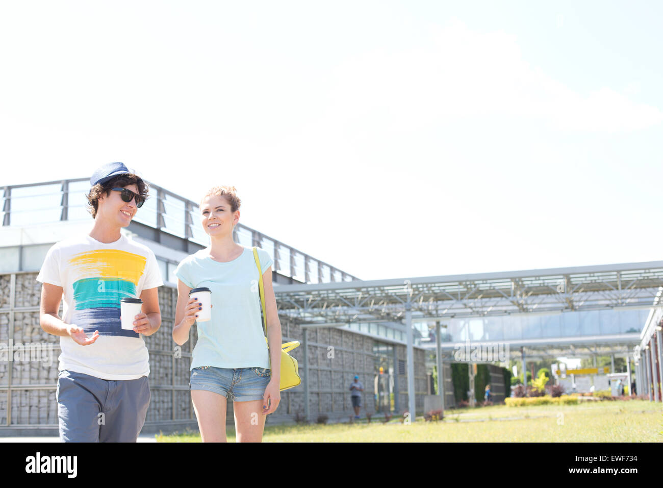 Smiling couple holding disposable cups while walking at park - Stock Image