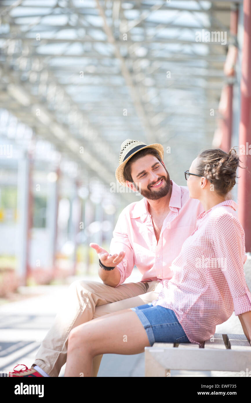 Happy man talking to woman while sitting on bench under shade - Stock Image