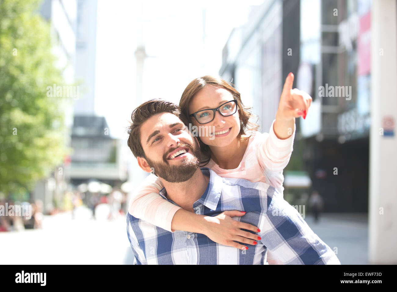 Cheerful woman pointing away while enjoying piggyback ride on man in city Stock Photo