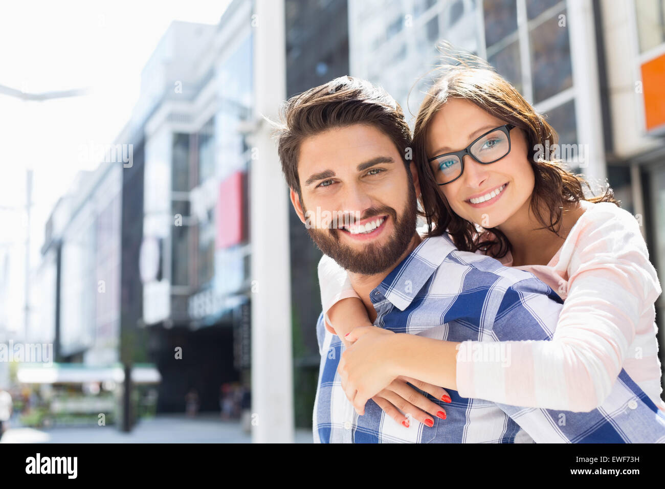 Portrait of happy man giving piggyback ride to woman in city Stock Photo