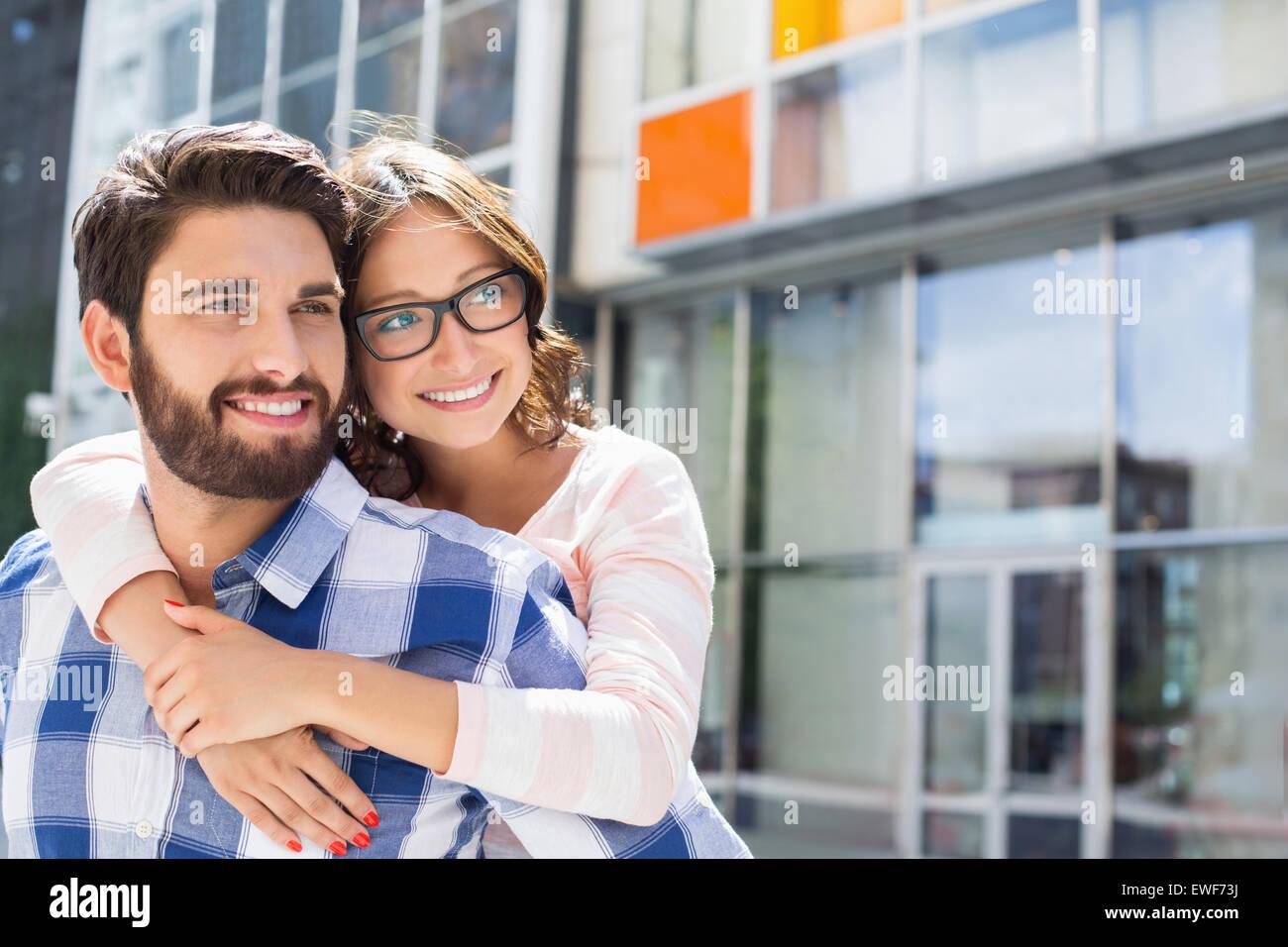Loving man piggybacking woman in city - Stock Image