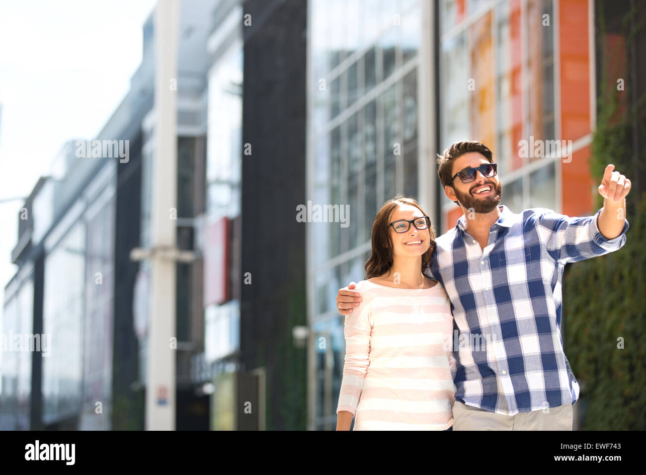 Happy man showing something to woman outside building - Stock Image