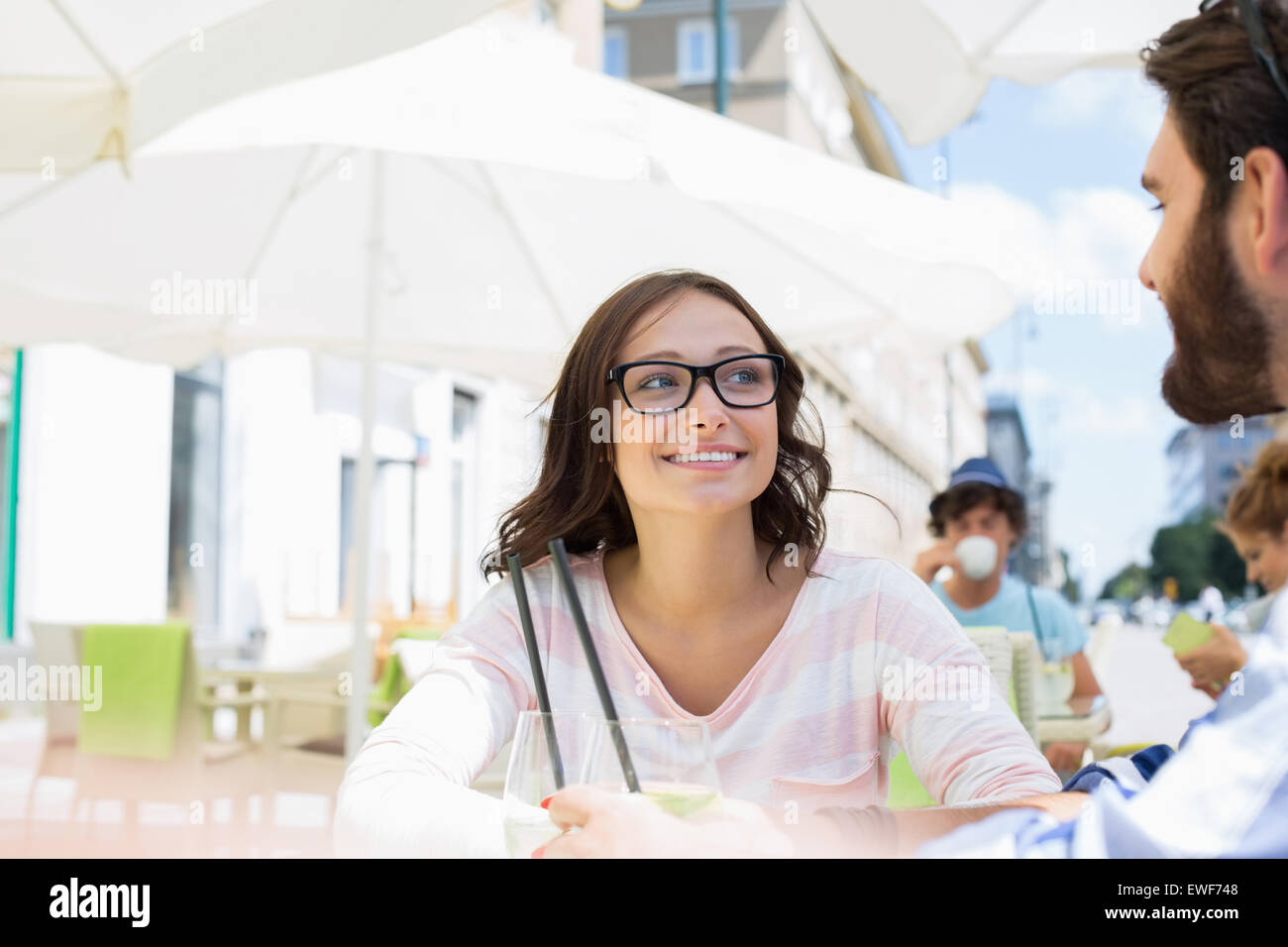 Smiling woman sitting with man at sidewalk cafe - Stock Image
