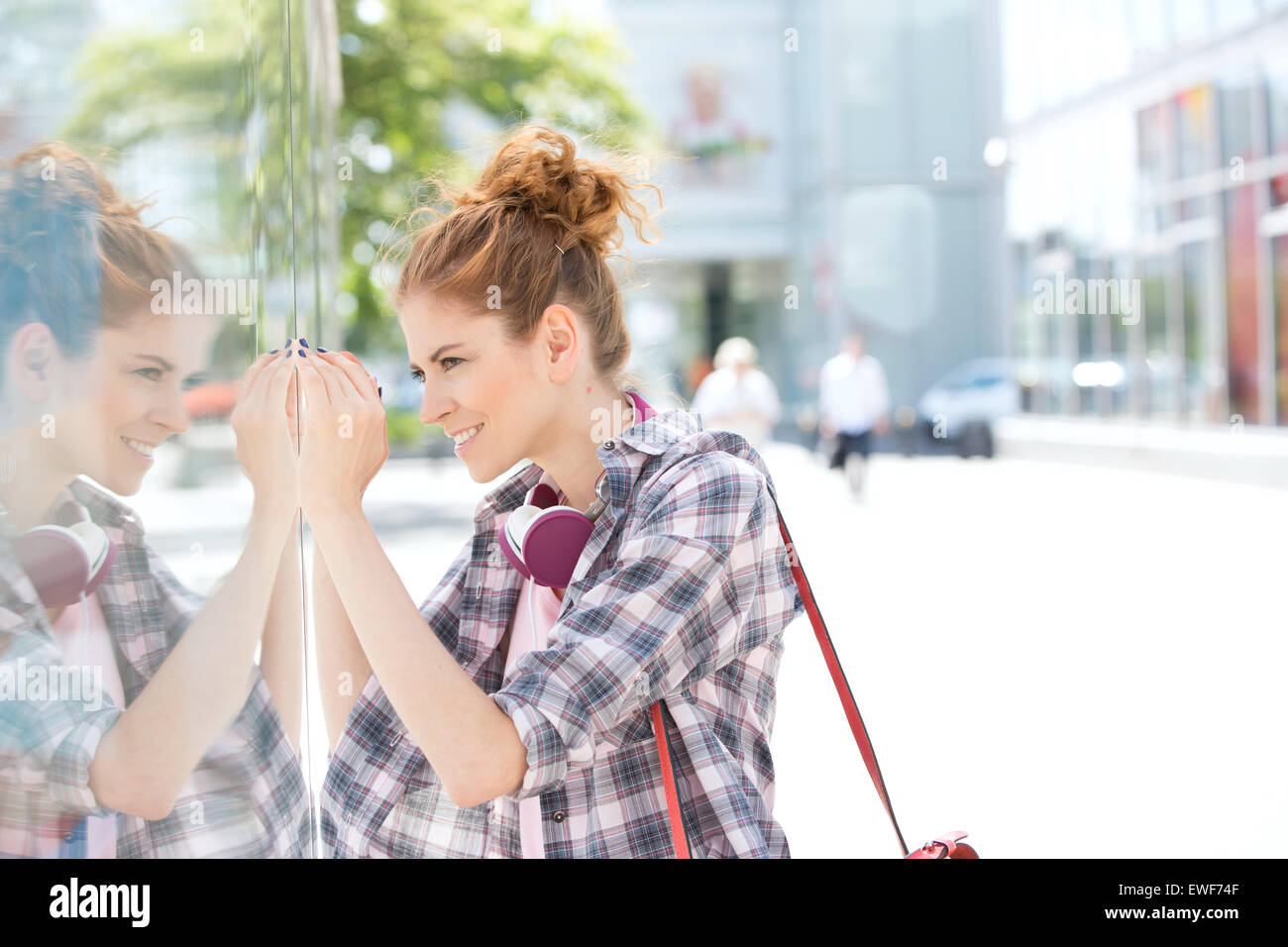 Side view of happy woman window shopping in city - Stock Image