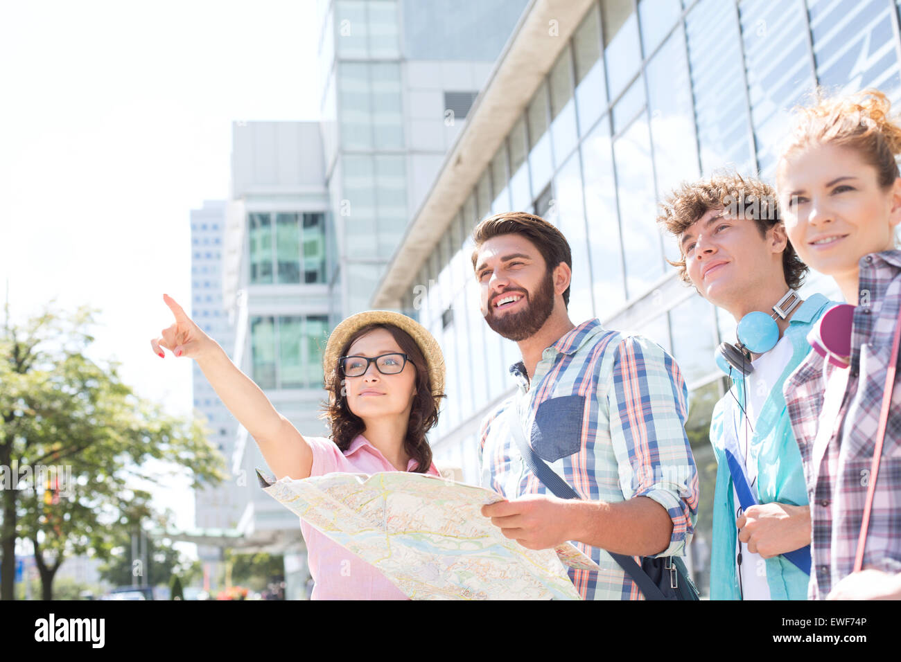 Happy friends with road map with woman pointing away in city - Stock Image