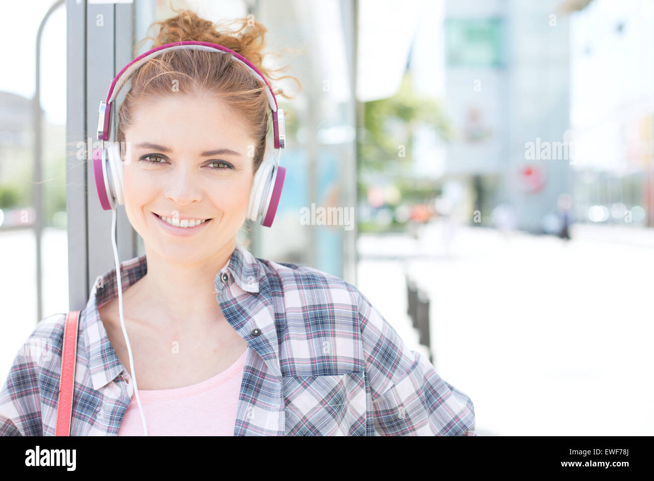 Portrait of happy woman wearing headphones while waiting at bus stop - Stock Image
