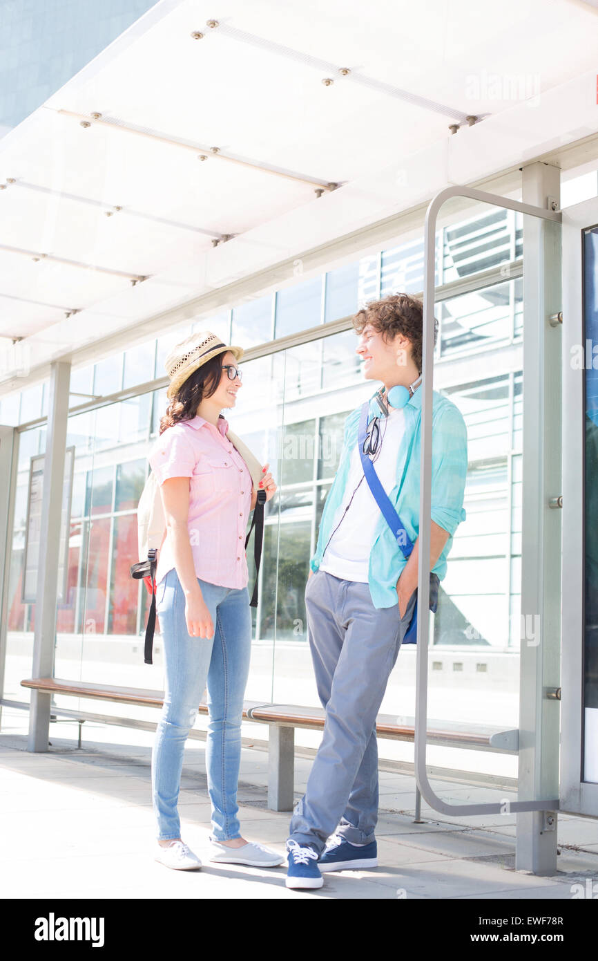 Couple communicating while waiting at bus stop - Stock Image