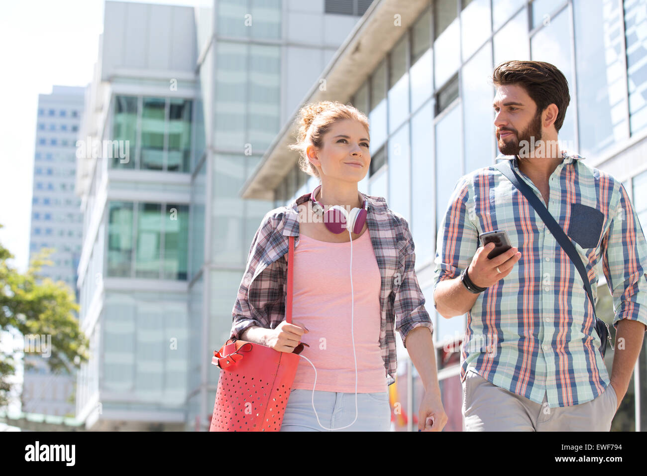 Male and female friends walking outside office building on sunny day - Stock Image