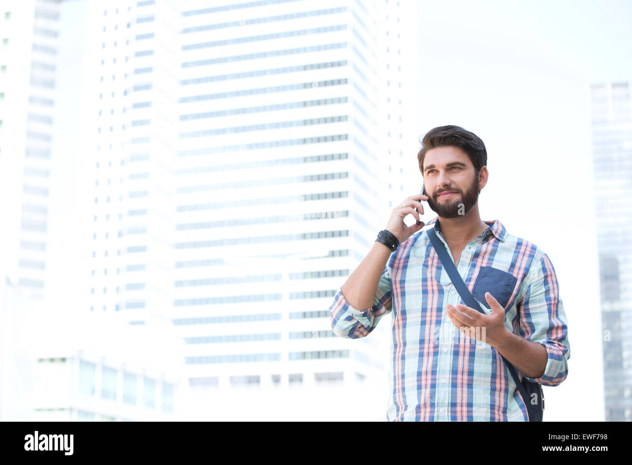 Smiling man gesturing while using cell phone in city - Stock Image