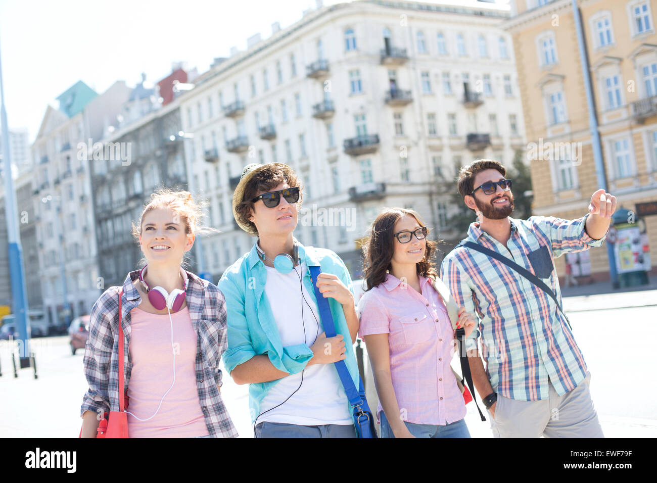 Happy man showing something to male and female friends on city street - Stock Image