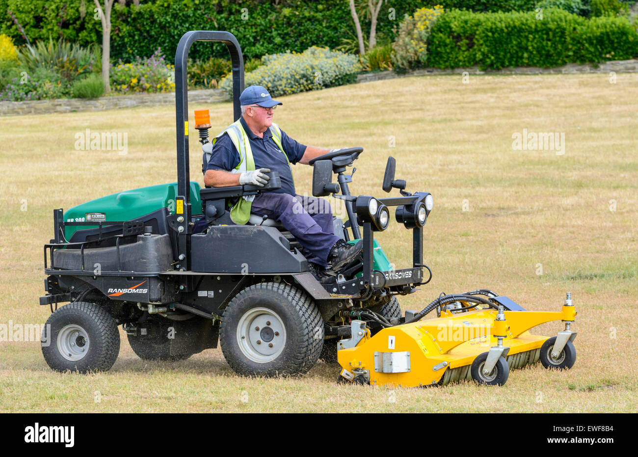 Old man riding on a Ransomes ride-on lawnmower while mowing and ...