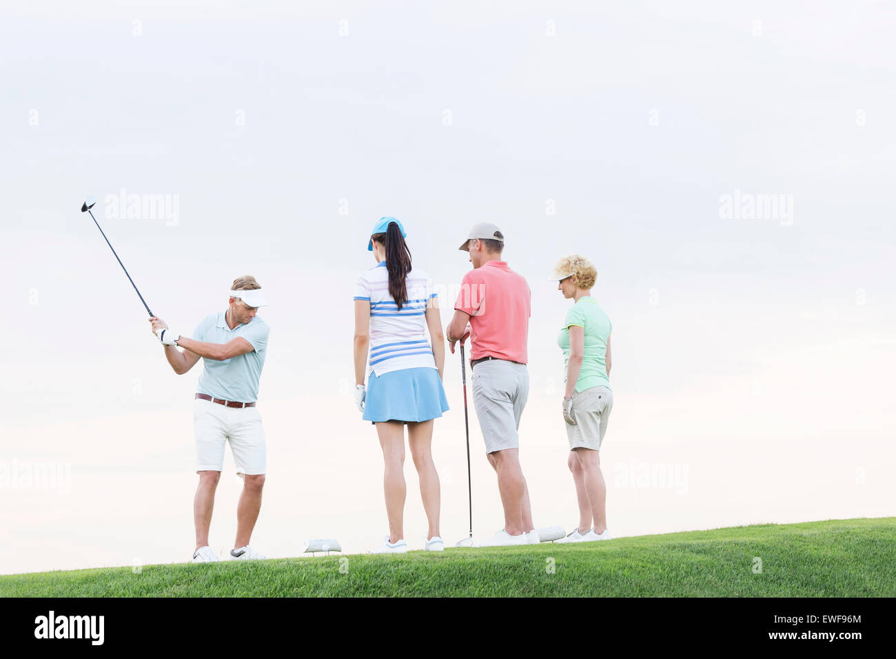 Group of friends looking at man playing golf against clear sky Stock Photo