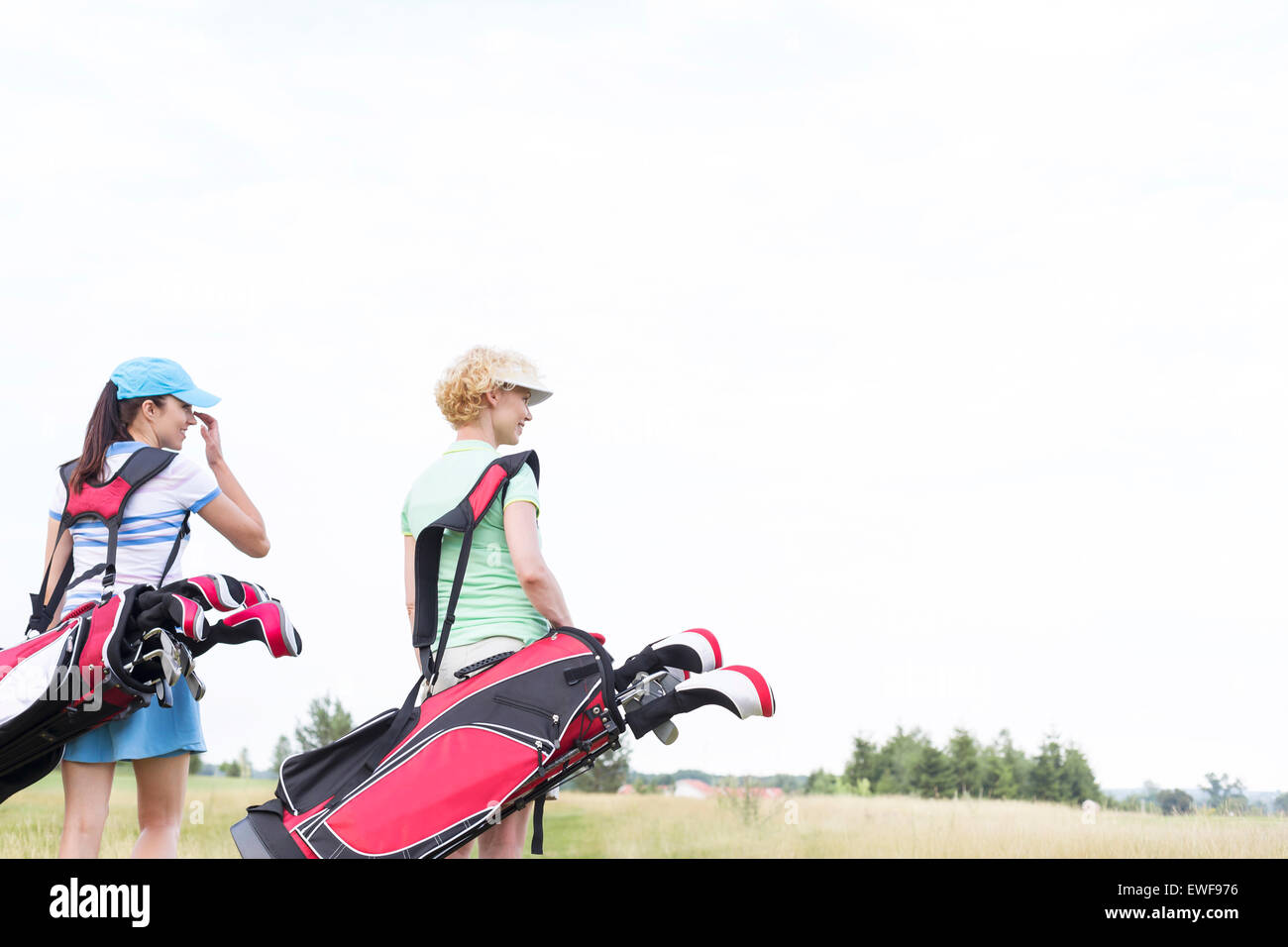 Rear view of women with golf club bags at course against clear sky - Stock Image