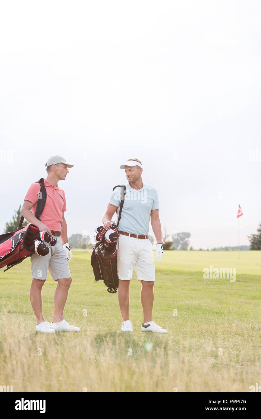 Full-length of men conversing at golf course against clear sky - Stock Image
