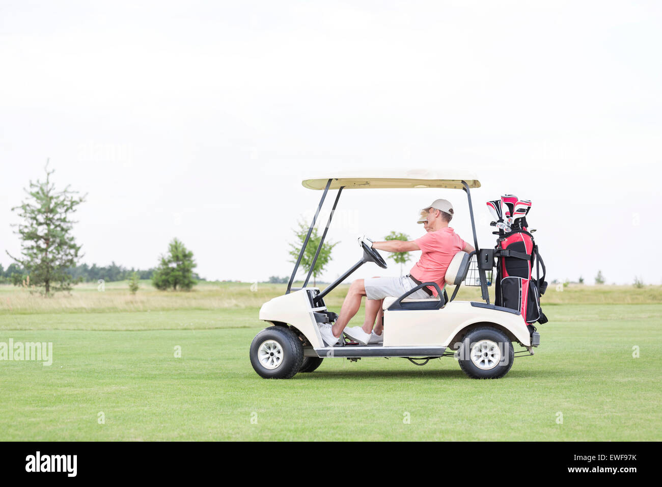 Side view of couple sitting in golf cart against clear sky - Stock Image
