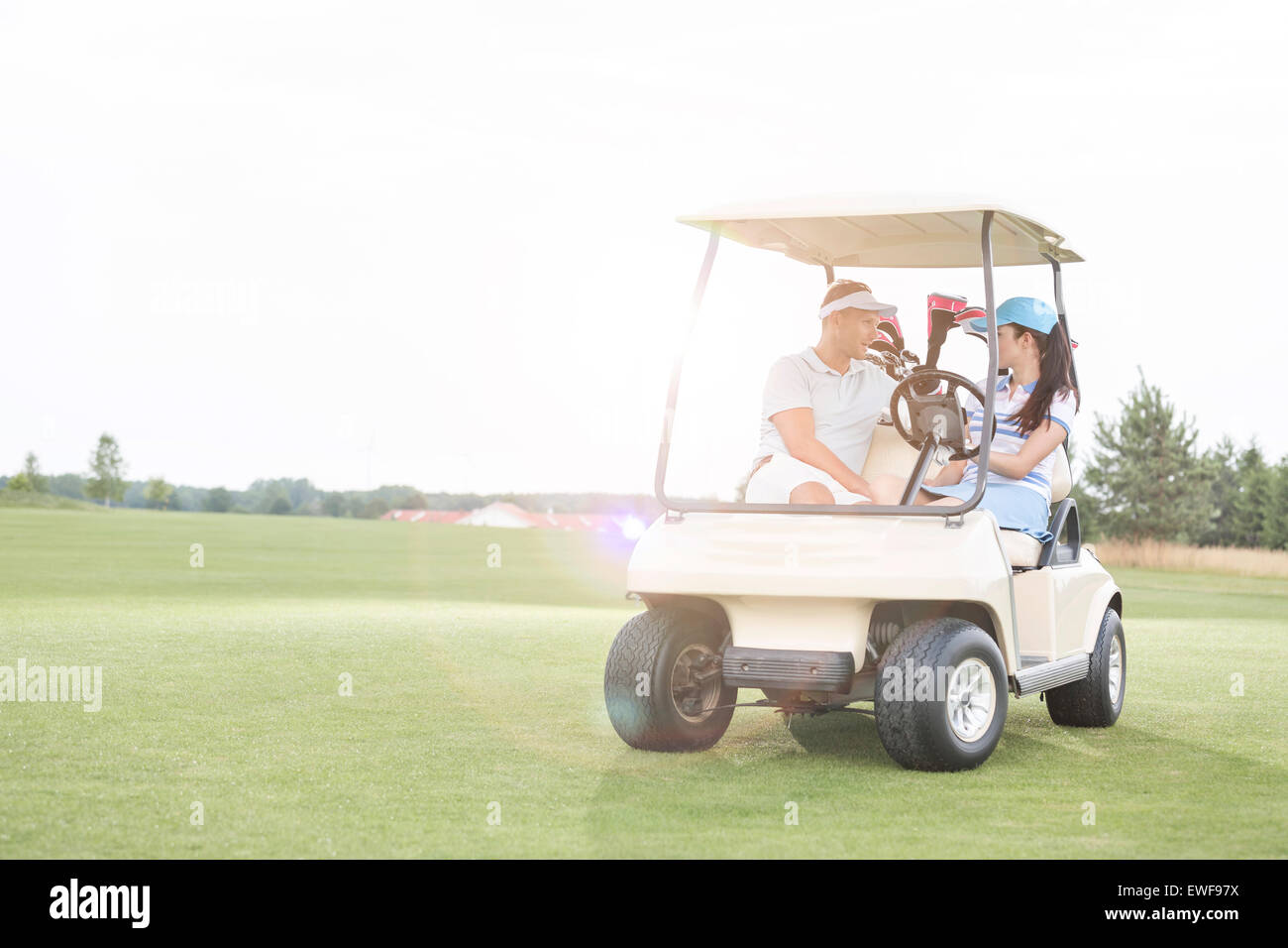 Couple looking at each other while sitting in golf cart against clear sky - Stock Image