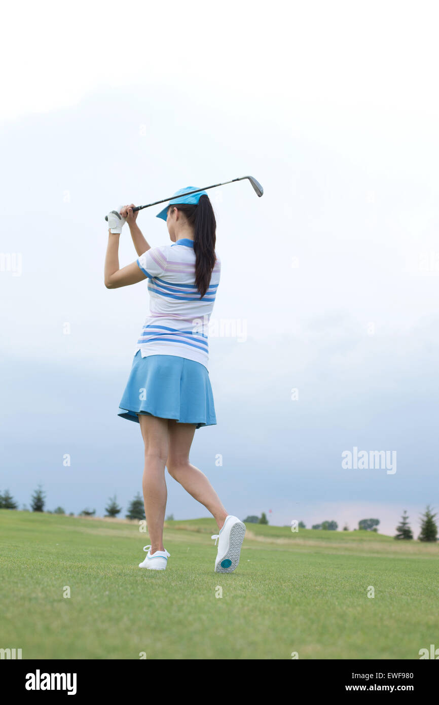 Rear view of woman swinging golf club at course - Stock Image