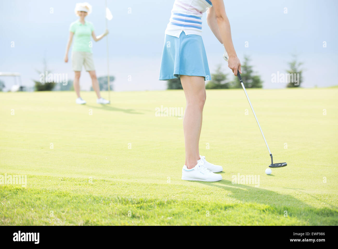Low section of woman playing golf with female friend - Stock Image