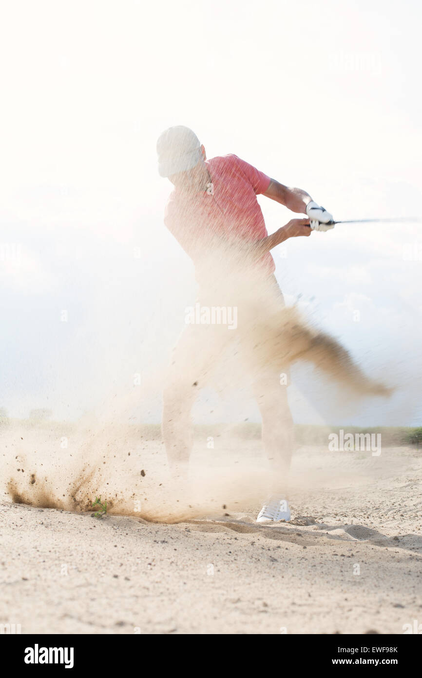 Middle-aged man splashing sand while playing at golf course - Stock Image