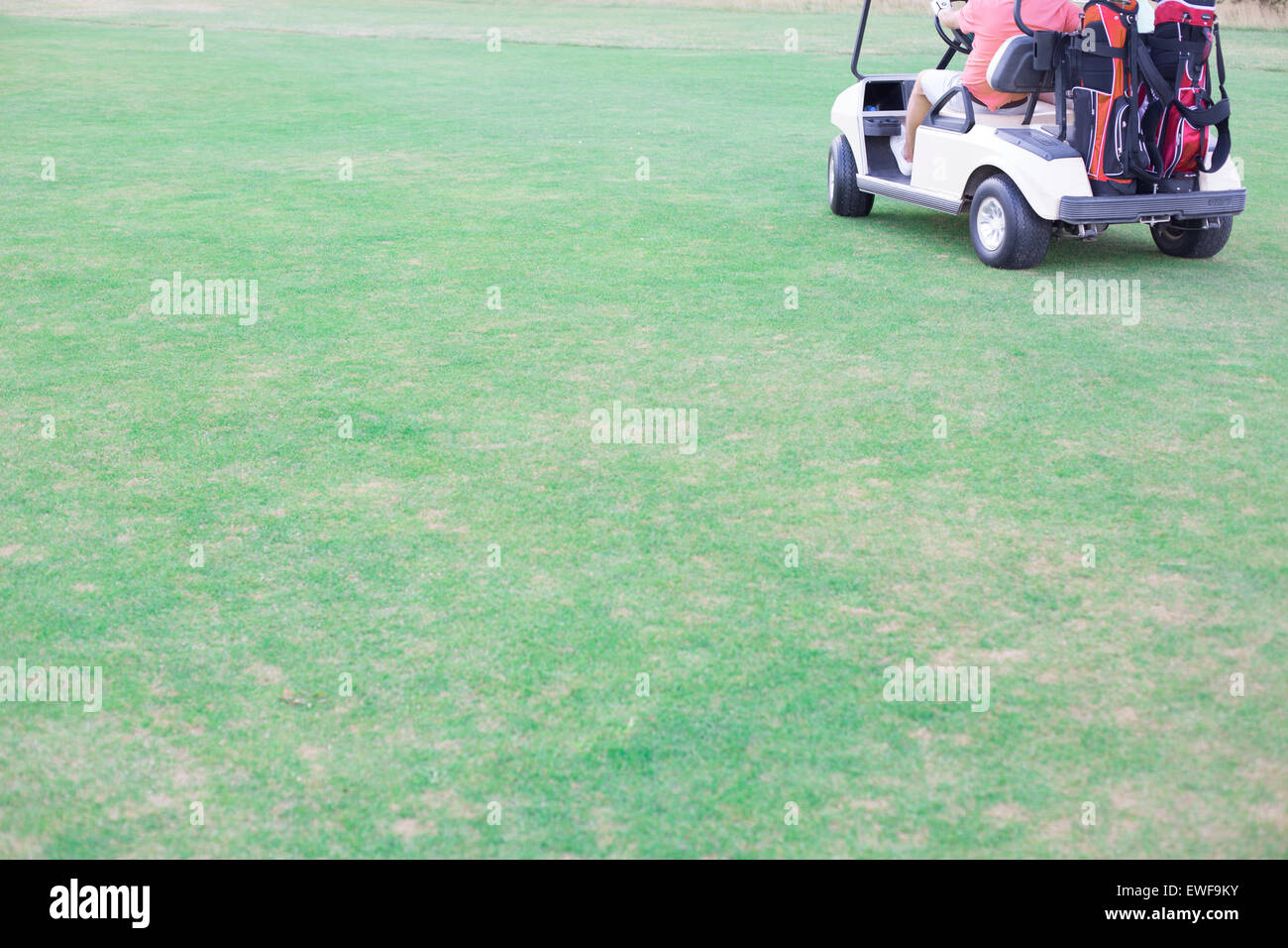 Low section of middle-aged man driving golf cart - Stock Image