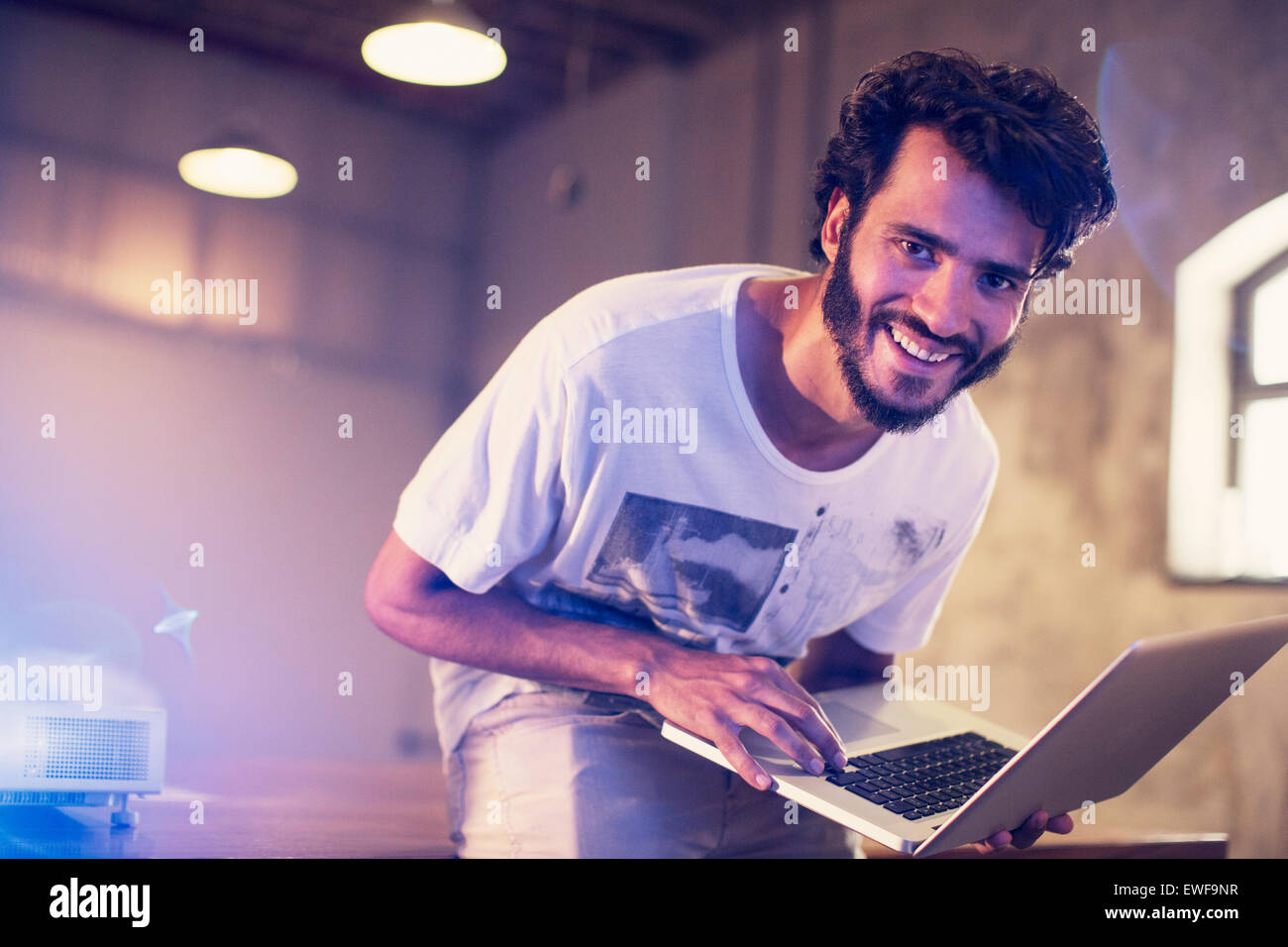 Portrait enthusiastic casual businessman with laptop in office - Stock Image