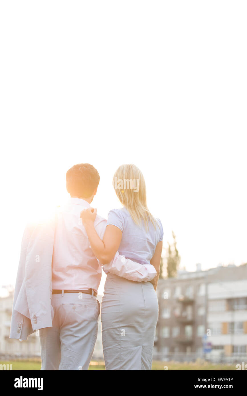 Rear view of business couple standing with arms around against clear sky on sunny day - Stock Image