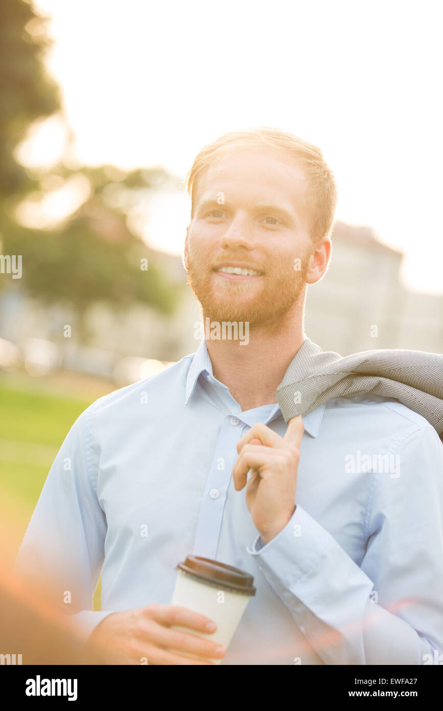 Happy businessman holding disposable cup outdoors - Stock Image