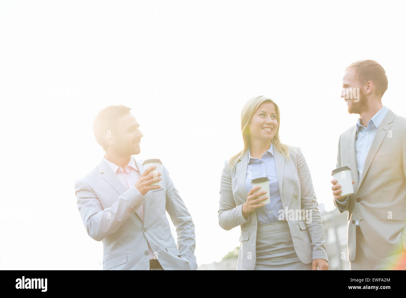Businesspeople with disposable cups talking against clear sky on sunny day - Stock Image