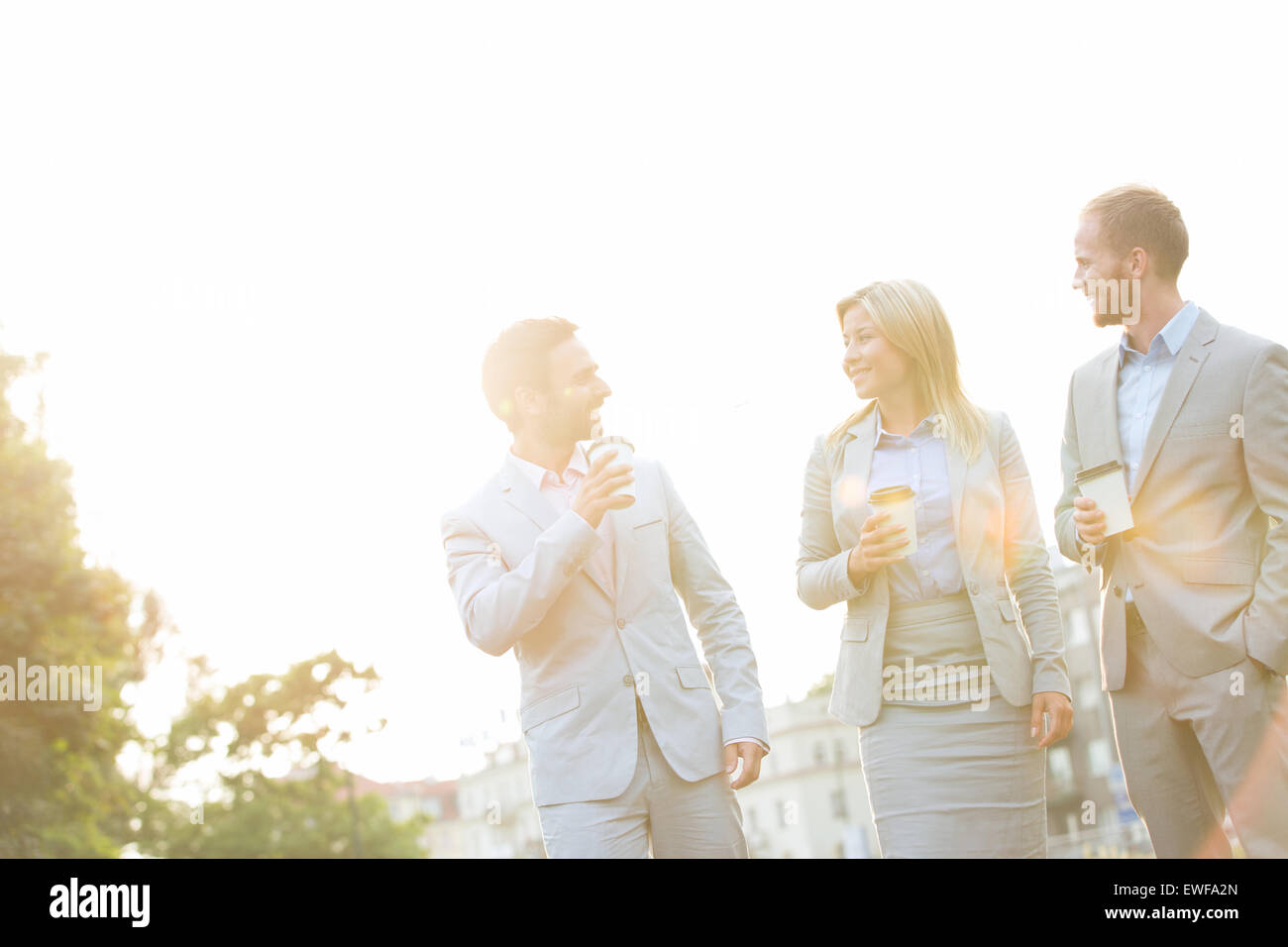 Businesspeople with disposable cups conversing against clear sky on sunny day - Stock Image
