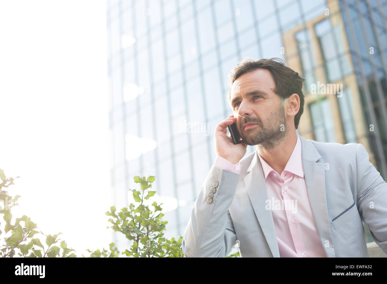 Businessman answering mobile phone outside office building - Stock Image
