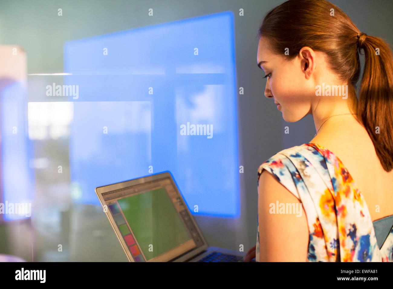 Businesswoman with laptop preparing audio visual presentation - Stock Image
