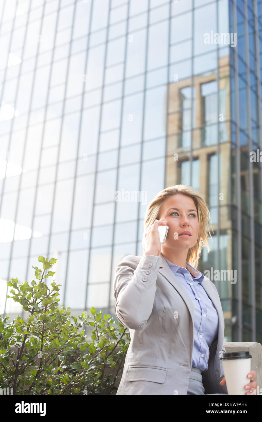Businesswoman using mobile phone outside office building - Stock Image