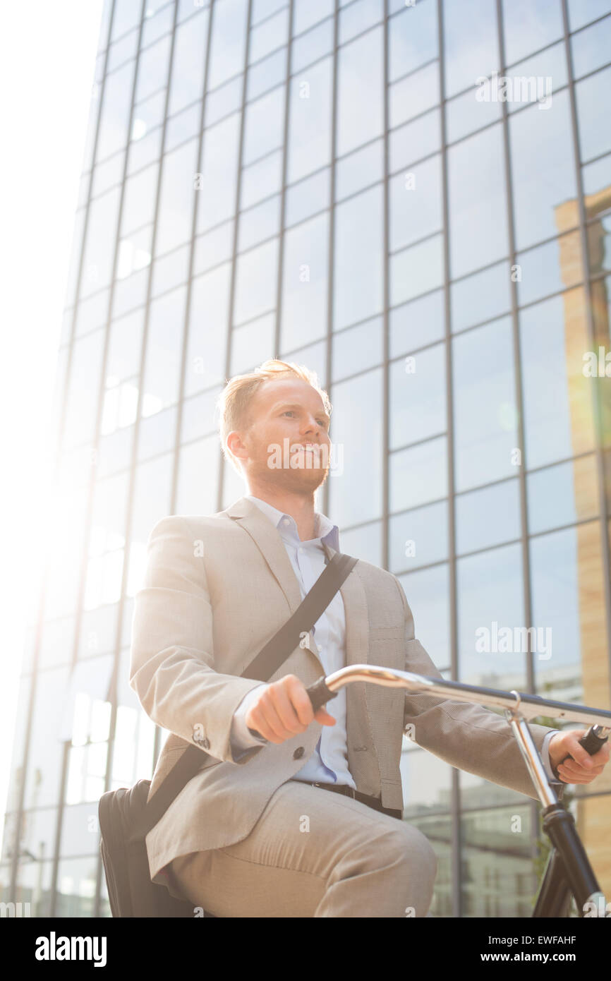 Low angle view of businessman riding bicycle outside office building on sunny day - Stock Image