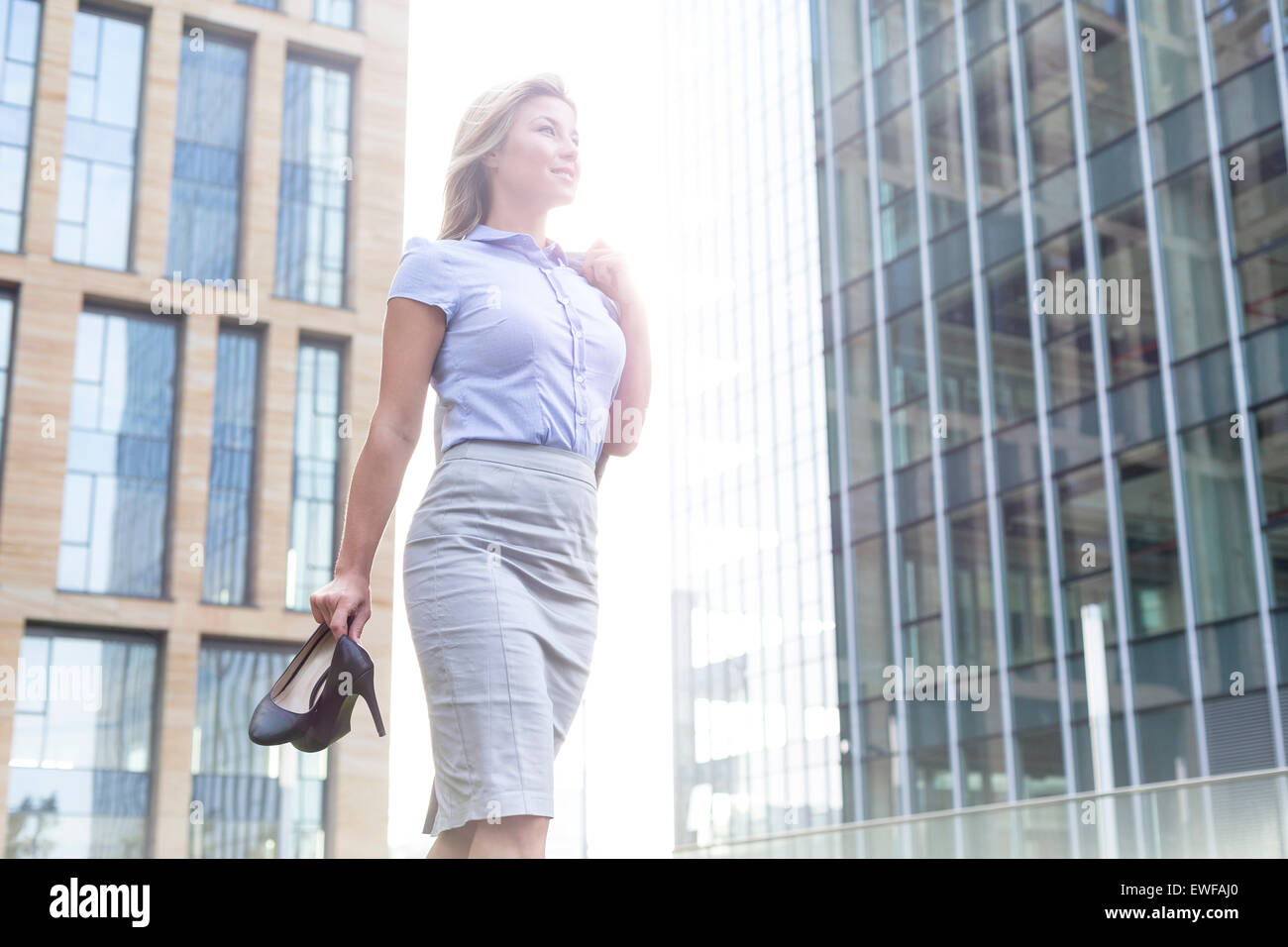Low angle view of confident businesswoman holding high heels while standing outside office buildings - Stock Image