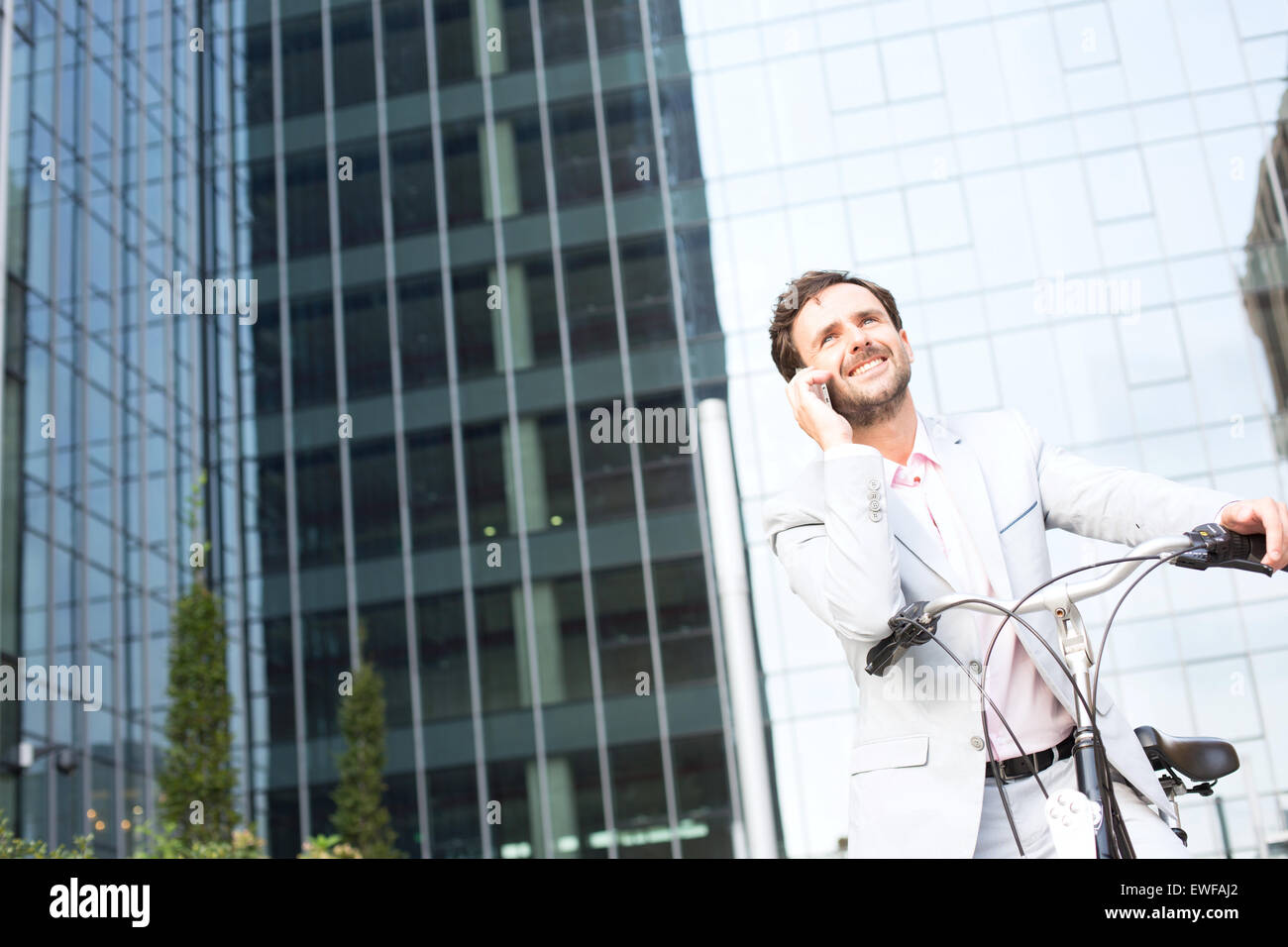 Low angle view of businessman answering mobile phone while sitting on bicycle outdoors - Stock Image