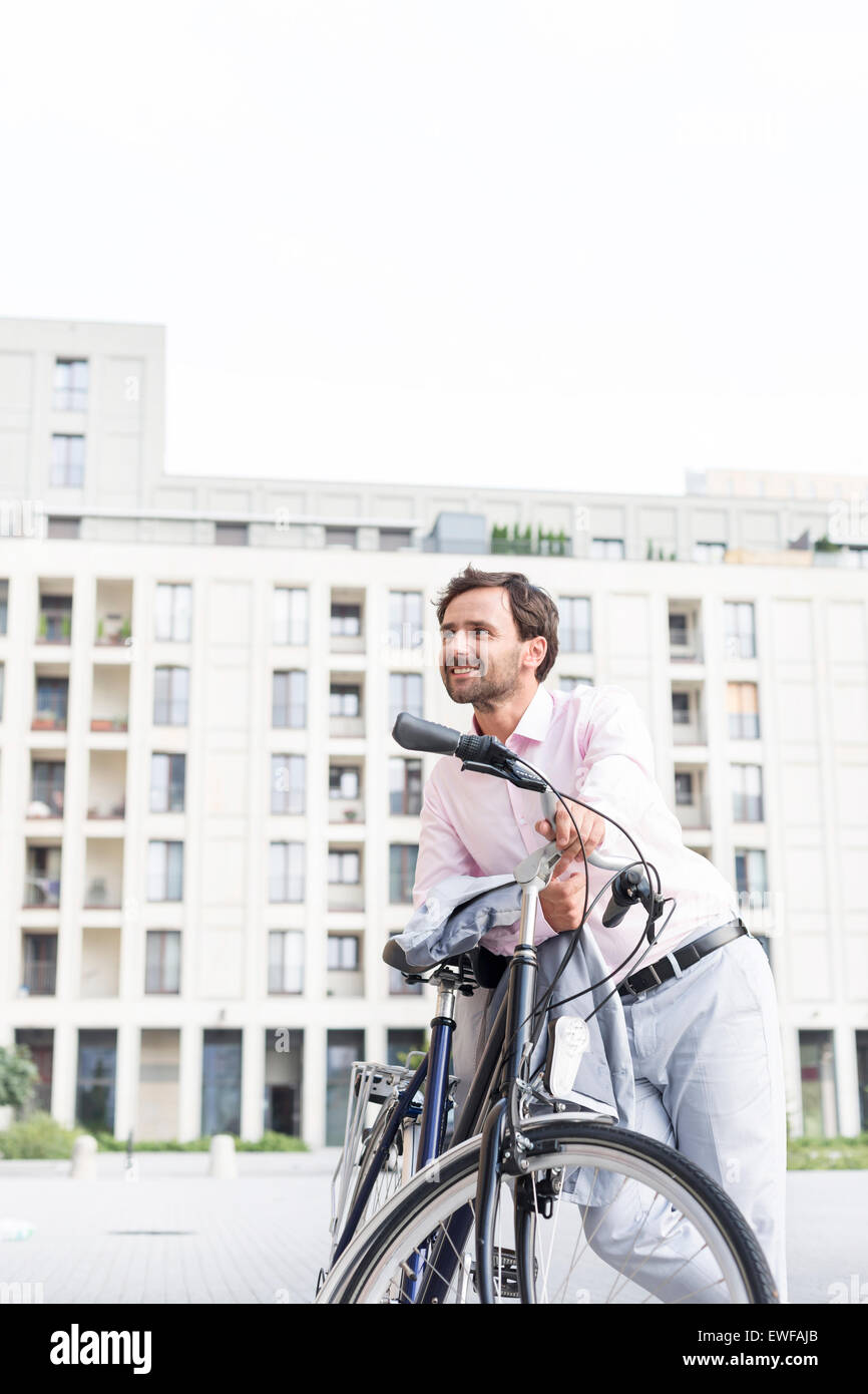 Thoughtful businessman leaning on bicycle outdoors - Stock Image